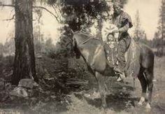 Spokane woman on horseback with infant in baby carrier, 1899. Colville ...