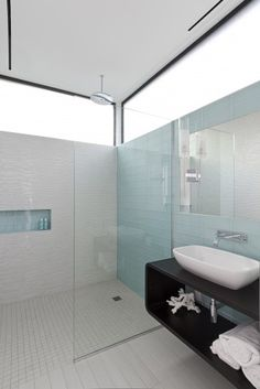 long, horizontal high window in shower/bath. stacked rectangular floor + wall tile. mirror inset into wall tile. wall-mounted faucet.