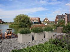 Deze moderne tuin in Utrecht ligt rondom een vrijstaande nieuwbouwwoning. Diverse terrassen, strakke hagen, grote plantenbakken vormen de basis.