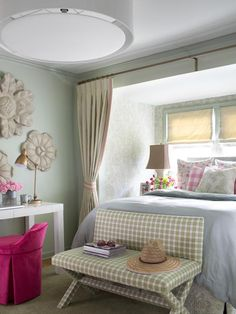 To keep the bedroom cool and calm, a light shade of pistachio green was used on the ceiling, trim and walls. To create a sense of depth in the nook, the walls were upholstered in a large-scale botanical fabric in a darker shade of pistachio.