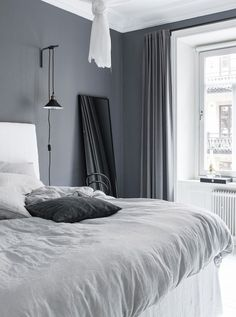 Grey shades in old building bedroom. Walls are painted in dark grey. The bed is white with a light grey blanket