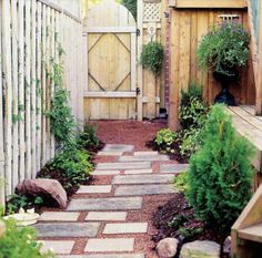 Pathway -- Geometrical Garden Path -- A tidy urban backyard is the perfect home for this square and shapely route through minimal plantings from deck to garden gate. In this yard, composite stone tiles create a happy hopscotch pattern in a pea gravel bed.