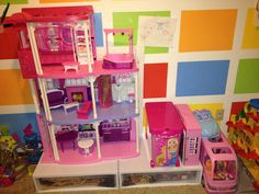 Plastic storage drawers underneath the Barbie Dream House.