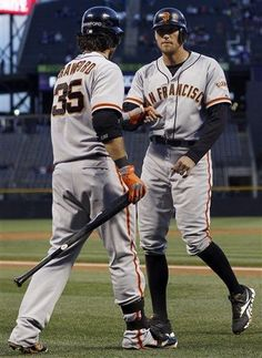 San Francisco Giants' Brandon Crawford, left, congratulates Hunter Pence after he scored on a single by Hector Sanchez against the Colorado Rockies in the first inning of a baseball game in Denver, Wednesday, Sept. 12, 2012