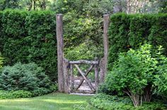 This rustic gate has an arborvitae hedge for a fence on either side.  A Planters design.  Highlands, NC