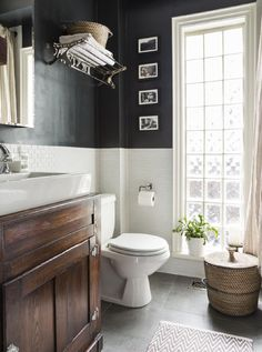 Black walls are dramatic yet paired with the white tile the room still feels spacious