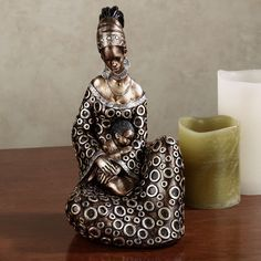 Thankful for all her Blessings, this Masai woman is truly grateful. Resin figurine depicts an African woman holding a young child. She is wearing earrings and a brushed bronze dress accented with silver circles. African American Art, African Women, Animal Print Bedding, Bronze Dress, African Tattoo, African Sculptures, African Home Decor, Fairy Figurines, Black Figurines