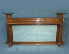 A lovely Arts and Crafts over mantle mirror  Solid mahogany frame  Original large rectangular bevel edged mirror  Lovely pierced spade decoration to top posts, front turned columns to either side  Measures approx   75 cms High   143 cms Wide   17 cms Deep