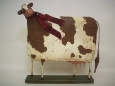 This sweet cow stands 10 inches high and is 10 inches long and is made from a paper mache/sawdust mixture and some heavy wire and wood. She