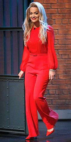 Last Night's Look: Love It or Leave It? Vote Now! | RITA ORA | wearing a bright red long-sleeve jumpsuit by MaxMara with matching scarlet pumps for a stop at Late Night with Seth Meyers in N.Y.C.