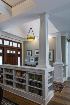 This creative storage space was designed by TriplePoint Design Build to accommodate books and living room knickknacks in the entryway of this remodeled home. The bookcases and columns, which were painted white to match to ceiling and trim of the home, divide the foyer from the living room. The size of the cubby space mirrors the sidelight cutouts above the front door for an interesting effect.