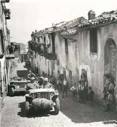 """""""1943- Natives of Pollina, Sicily, watch American soldiers and their vehicles moving along in a narrow street after the town fell to the Allies. Note surge tank on front jeep."""""""