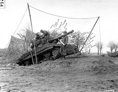 "Sgt. Earl F. Scholz, Pvt. George E. Van Horne, and Pfc. Samuel R. Marcum (from left to right) of the Battery C, 702nd Tank Destroyer Battalion, US 2nd Armored Division (""Hell on Wheels"") with a M36 Jackson tank destroyer. It is on a dug-in ramp so it has plenty of elevation to hurl shells at long range enemy targets across the Roer River, Belgium, Dec. 16, 1944."
