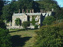 """Langdon Court, Wembury, South Devon is recorded in the Domesday Book of 1087 as having been a double manor amongst the 107[2] Devon holdings granted to Juhel de Totnes (d. 1123/30), feudal baron of Totnes,[1] by William the Conqueror for his support during the Norman Conquest of England in 1066. Before 1066 one part had been held by Heche (or """"Heca""""), the other by Gode (or """"Goda""""). Juhel in turn granted both parts of Langdon to one of his knights named Waldi"""