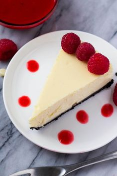 Smooth, creamy White Chocolate Cheesecake with an Oreo cookie crust and Raspberry Coulis Sauce. With easy step by step instructions - it's the PERFECT cheesecake every time!
