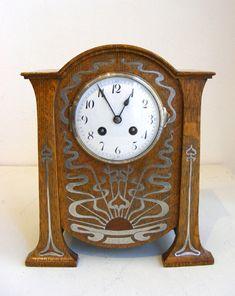 Reloj de madera con incrustaciones y la decoración de peltre que representa un sol naciente. Libertad