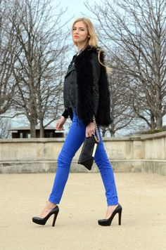 streetstyle fashion - fur vest, leather jacket and royal blue skinny jeans