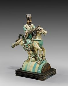 """ANTIQUE POTTERY EQUESTRIAN ROOFTILE Antique Chinese Ming-style, crackle-glazed roof tile; 19th Century or earlier: in the form of an equestrian official with tall hat, riding on a highly animated horse; in cream and turquoise glaze with good iridescence; H: 16 1/2""""; wood stand Ridge Tiles, Roof Decoration, Tall Hat, Roof Cleaning, Glazed Tiles, Antique Pottery, Roof Tiles, China Art, Chinese Ceramics"""