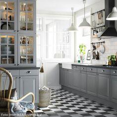 Die graue Einbauküche lässt den romantischen Landhausstil cool wirken. Zusammen mit den schwarz-weißen Fliesen ist die Küchengestaltung klassisch und…