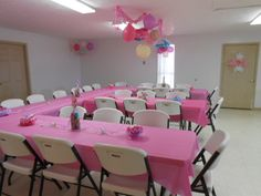 Tables covered in pink plastic tablecloths and decorated with baby bottle centerpieces, baby confetti, stuffed animals and pink sparkly mesh. Plastic Table Covers, Plastic Tablecloth, Plastic Tables, Tablecloth Ideas, Baby Shower Backdrop, Diy Backdrop, Bottle Centerpieces, Baby Shower Prizes, Butterfly Baby Shower