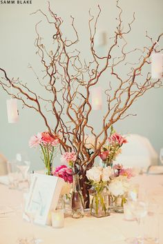 Branches with low blooms., great way to have a natural twig look w/ an of accent of flowers to soften the look, add a few hanging light or crystal & change up the look, just ask us, we love to be different.     Elegant Designs By Joy