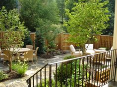 The custom wood privacy fence surrounds a flagstone patio interspersed with small beds of low maintenance plantings in Bethesda, MD