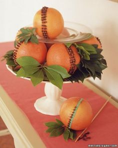 Place a rubber band around middle of a pink grapefruit or orange & make an even ring of cloves around fruit, piercing the skin first with a nail. Remove rubber band & make more rows. Use a hot-glue gun to attach star anise. To dry pomanders & retain scent, shake in a plastic bag of powdered orrisroot (available at health-food stores) before displaying. Stack the pomanders in a pyramid, using clear plates between the layers and tucking in greenery,as you go.