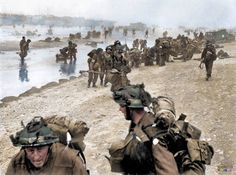 Troops of 3rd Infantry Division on Queen Red beach, Sword area, circa 0845 hrs, 6 June 1944. In the foreground are sappers of 84 Field Company Royal Engineers, part of No.5 Beach Group, identified by the white bands around their helmets. Behind them, medical orderlies of 8 Field Ambulance, RAMC, can be seen assisting wounded men. In the background commandos of 1st Special Service Brigade can be seen disembarking from their LCI(S) landing craft.