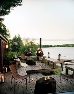 Deck overlooking lake with a fire pit and candles.  Love these chairs.