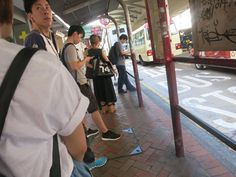a bus station with people waiting for the bus in Hong Kong