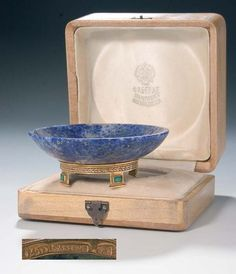 "A lapis lazuli salt cellar. Mounted upon a gold base set with four emeralds. Marked ""FABERGE"" in Cyrillic, 72 standart, master's mark ""M.P"" in Cyrillic. In fitted wood case stamped ""FABERGE S. Petersburg, Moscow, Odessa"". Diam. 6,8 cm."