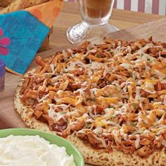 Slumber Party Pizza: 1 prebaked 12-inch pizza crust  3 cups shredded cooked chicken  1 cup barbecue sauce  1 cup (4 ounces) shredded part-skim mozzarella cheese  1/2 cup shredded cheddar cheese  Minced fresh parsley *Place crust on a 14-in. pizza pan. Combine chicken and barbecue sauce; spread over crust. Sprinkle with cheeses.  Bake at 450° for 8-10 minutes or until cheese is melted. Sprinkle with parsley.Yield:8 slices.