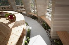 Peanuts Nursery in Japan. Indoor-outdoor - pathways, pebbles and shrubbery brings the outdoors in.