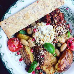 Vitlöksrostad potatis, citronmarinerade vita bönor, tomatpesto, kaprissås, granatäpple, rostade hasselnötte, pumpakärnor, sesamfrön, tomat, basilika, hackad soltorkad tomat och bladspenat