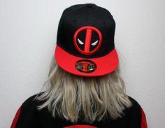 """Bereit für pechschwarzen Humor, grandiose Schwerteinlagen und actiongeladene Kampfszenen? Dann ab mit euch in die Welt von Deadpool. Damit du Deadpool auch gebührend Tribut zollen kannst, haben wir die schwarz/rote """"Logo"""" Snapback-#Cap von Deadpool am Start. Auf der Cap ist das typische #Deadpool Logo aufgestickt. Der rote Schirm macht die Cap dann perfekt. #empstyle"""