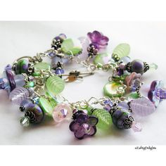 This fabulous loaded charm bracelet is built on a lovely sterling silver heart link chain. It has beautiful hand torched Lampwork glass beads in mixed purples and greens, vintage lucite beads, check glass flowers. They are combined with a lot of Sterling Silver caps and spacers, Swarovski Crystals, and a pretty Sterling floral toggle clasp.  ~<3K8<3~