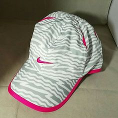 """NIKE Hot Pink, White with Grey Zebra Pattern Cap Brand: Nike Item: White with Gray Zebra Print & Hot Ink Featherlight Dri-Fit Exercise, Running Hat Cap Color: Hot Pink, White % Gray Measurements:  8"""" Opening, Brim is 2.75"""" Condition: Like New Pre-Loved Condition.  Please check my other listings for bundles to pay one shipping charge as I have a lot of small things listed. 10% off 4+ bundles YOU make. No lowballs. Nike Accessories Hats"""