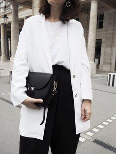 Paris Streetstyle at Palais Royal by Anaïs Eleni wearing Acne Studios Jensen Boots, black wide pants, white Mango blazer and Camelia Roma Celine lookalike bag.