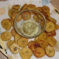 Tostones from Allrecipes.com ~ Plantains cut into one inch slices, fried, slightly mashed to half of an inch in thickness, fried once more, and then dusted with garlic powder and salt.