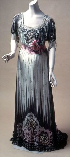 Evening gown, Mme. J. Baer, North America, ca. 1910. Black silk burnout chiffon trimmed with rhinestones & beads over white satin underdress. Wide pink ribbon sash & pink silk flower corsage at waist. Black & white rhinestone embellishment in vertical zigzag pattern on skirt; large floral pattern embroidered at hem; slight train. de Young/Legion of Honor/Fine Arts Museums of San Francisco