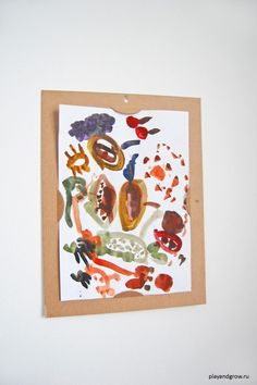 DIY Cardboard frame to display kids art. Use an exacto knife to cut semi-circles on each of the 4 sides. Artwork can easily be changed, as new ones come in!