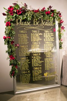 Mirror Seating Chart with Greenery + Red Florals | Photography: Charlie Juliet - www.charlie-juliet.com Read More: http://www.stylemepretty.com/2015/01/06/manhattan-wedding-at-glasshouses/