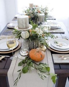 natural pumpkins, greenery and large candles on a fabric table runner