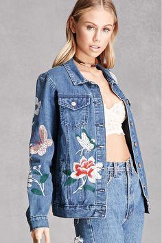 An oversized denim jacket by Pixie & Diamond™ featuring butterfly and floral embroidery throughout, buttoned front, basic collar, flap buttoned pockets, slit pockets, and long buttoned cuff sleeves.