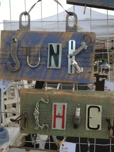 Hardware signs each made from salvaged barn wood.Various hardware was used to spell words made of hinges,license plate letters,spark plugs. Hooks are attached to bottom of each sign to help keep track of car keys and dog leash. JunkChic 5280