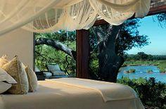 Cama con mosquitera y vistas a la sabana africana. • Lion Sands Resort in South Africa