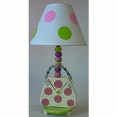 "Purse Lamp by Ababy. $69.00. Recommended Wattage: 60. 18"" H including shade. A Purse for HerOur Purse Lamp boasts an enticing appeal The polka dotted shade in pinks and greens is just the beginning. Down the stem of colorful balls, to the circular base resting on balled feet, a lovely purse sits - to bring delight to your little girl. A beaded handle adds the finishing touch. A lamp with character"