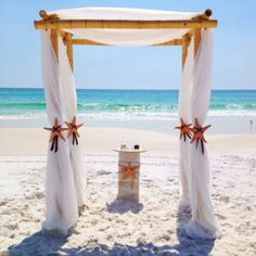 Bamboo four post arbor with white sheer fabric and starfish accents. Custom white wooden ceremony table for sand ceremony.  Decor designed by Bella Flora 30a