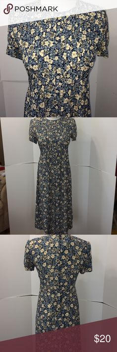 Flowered Dress Pre-loved short sleeve, round neck, maxi, blue and white flowered dress.  The background is navy blue with two-tone blue flowers and off white flowers.  There's rouging at the top and ends just below the bust.  This is a very flattering dress as it hides your stomach.  It has a zipper in the back as well as a tie.  This dress has shoulder pads. Size 4. Excellent condition. Dry clean ( and this item has been dry cleaned prior to selling) Dresses