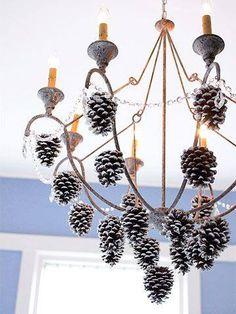 Dennenappels zijn erg leuk om te gebruiken als kerstdecoratie. Spuit ze wit en hang ze op met een mooi lint. Bijvoorbeeld zoals hier aan een kroonluchter.